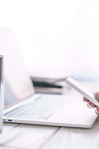 close up of white desk laptop clear glass of water with woman's hands holding phone