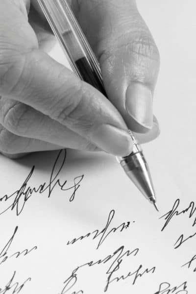 close up of woman writing a letter