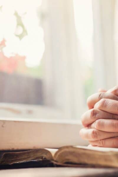 woman praying with open bible at window