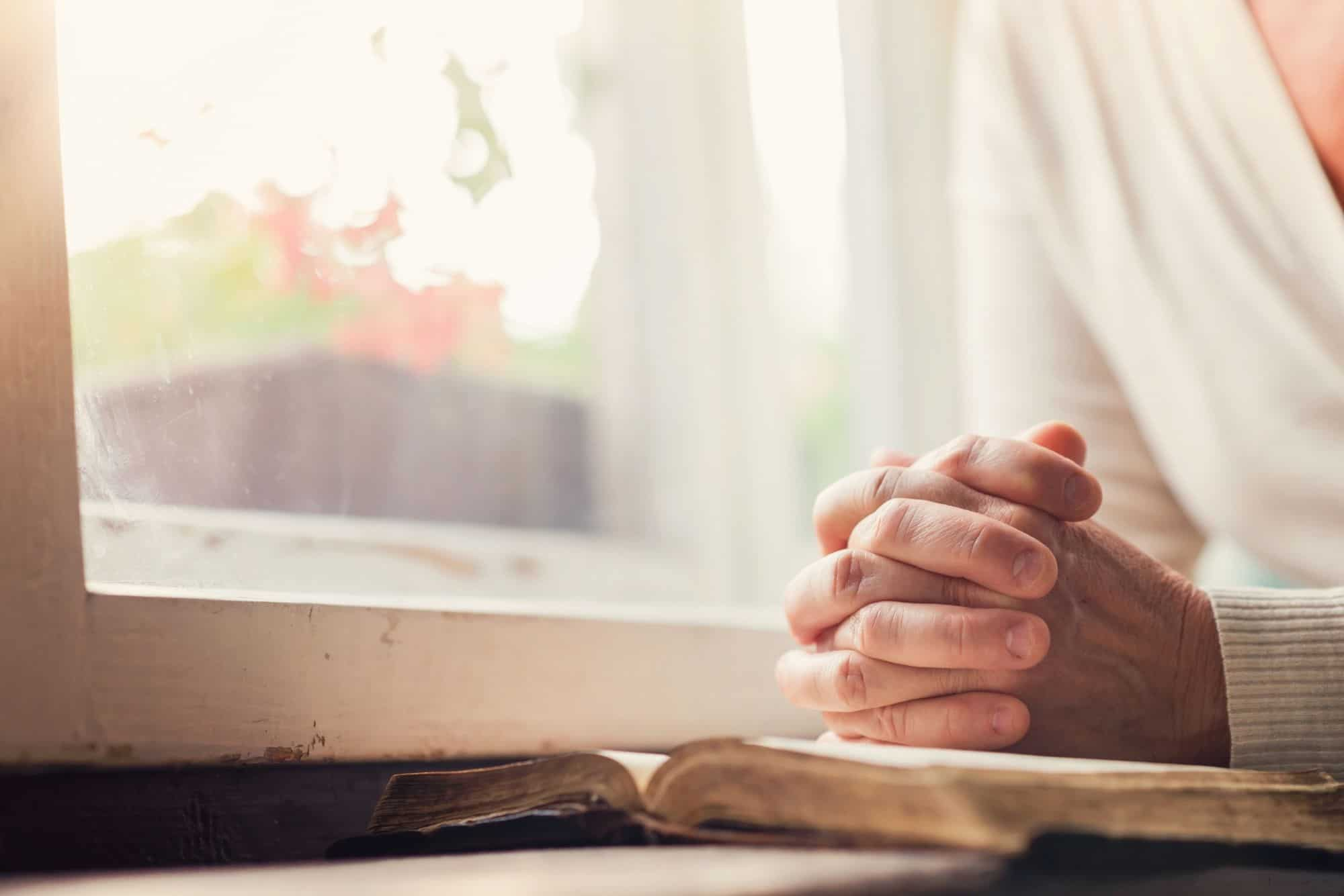 woman with open bible pray at window